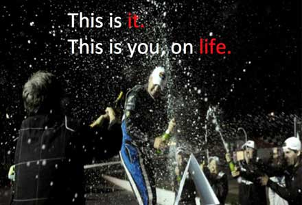 Photo of a race car driver popping a bottle of champagne with text
