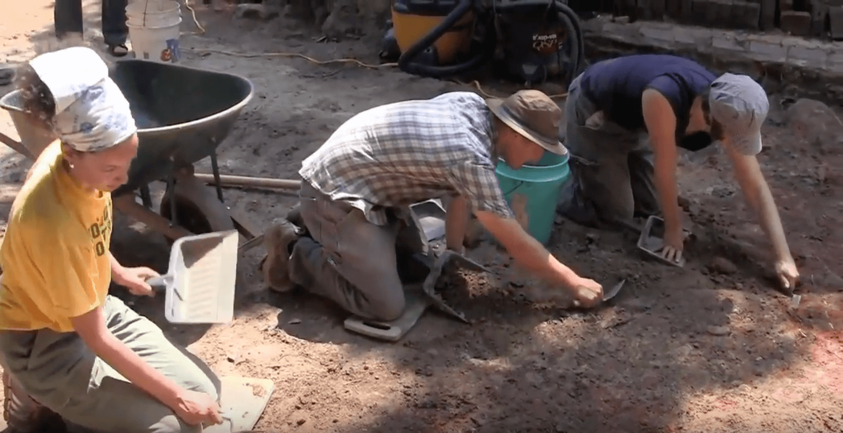 Three UNC archaeologists kneeling down with their tools in the dirt.