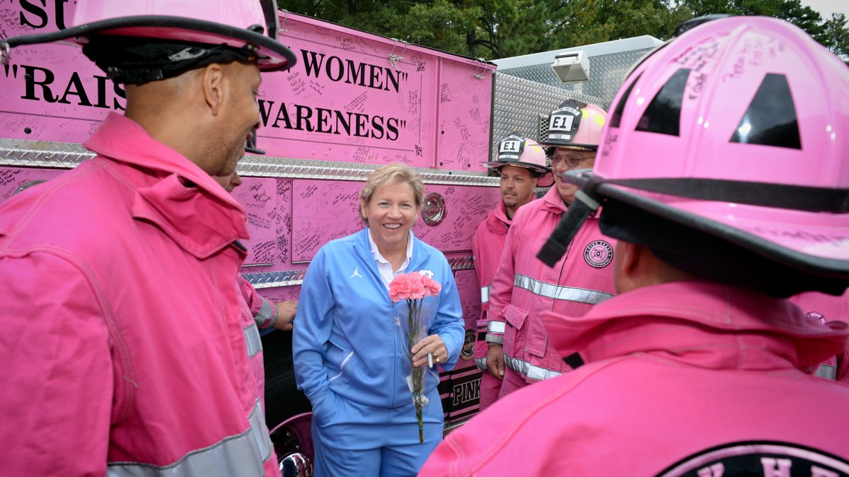 Sylvia Hatchell holds pink flowers and talks with firefighters dressed in pink uniforms