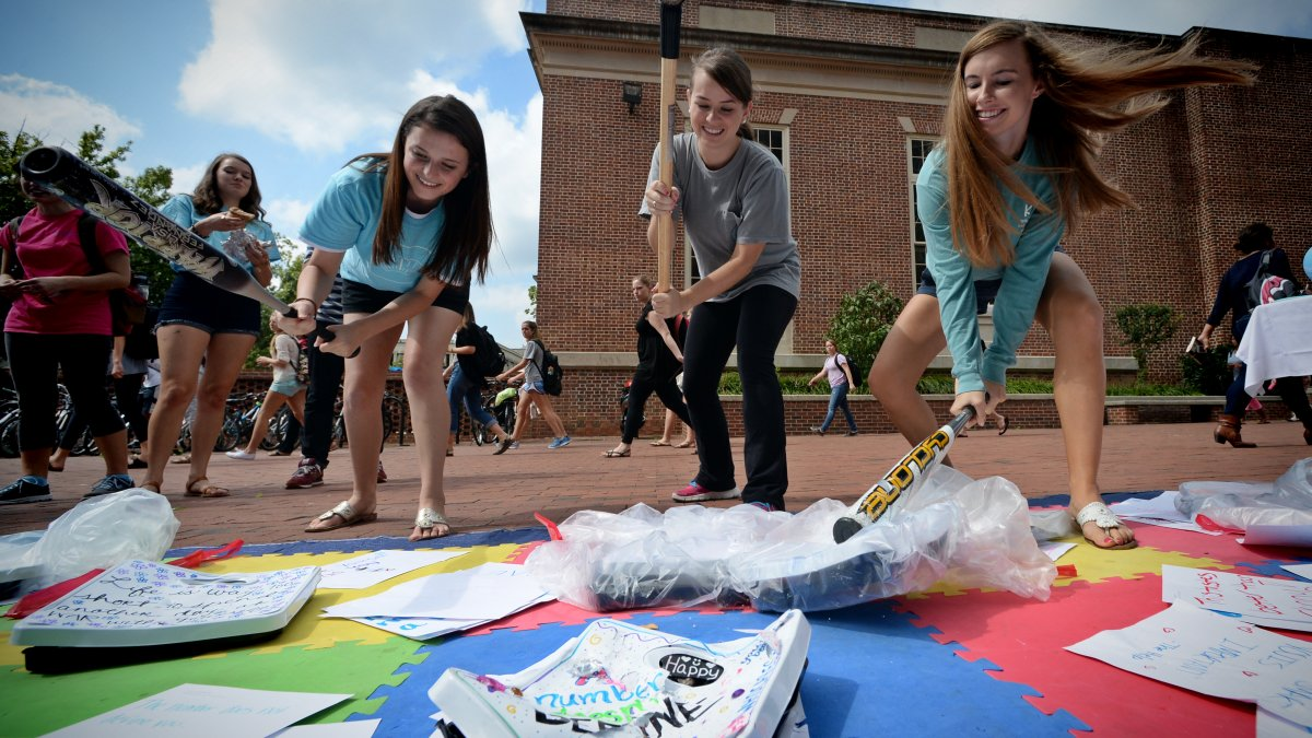 seniors Chloe Paterson, Emily Rodgers, and Laura Gilland use baseball bats to smash scales in the Pit.