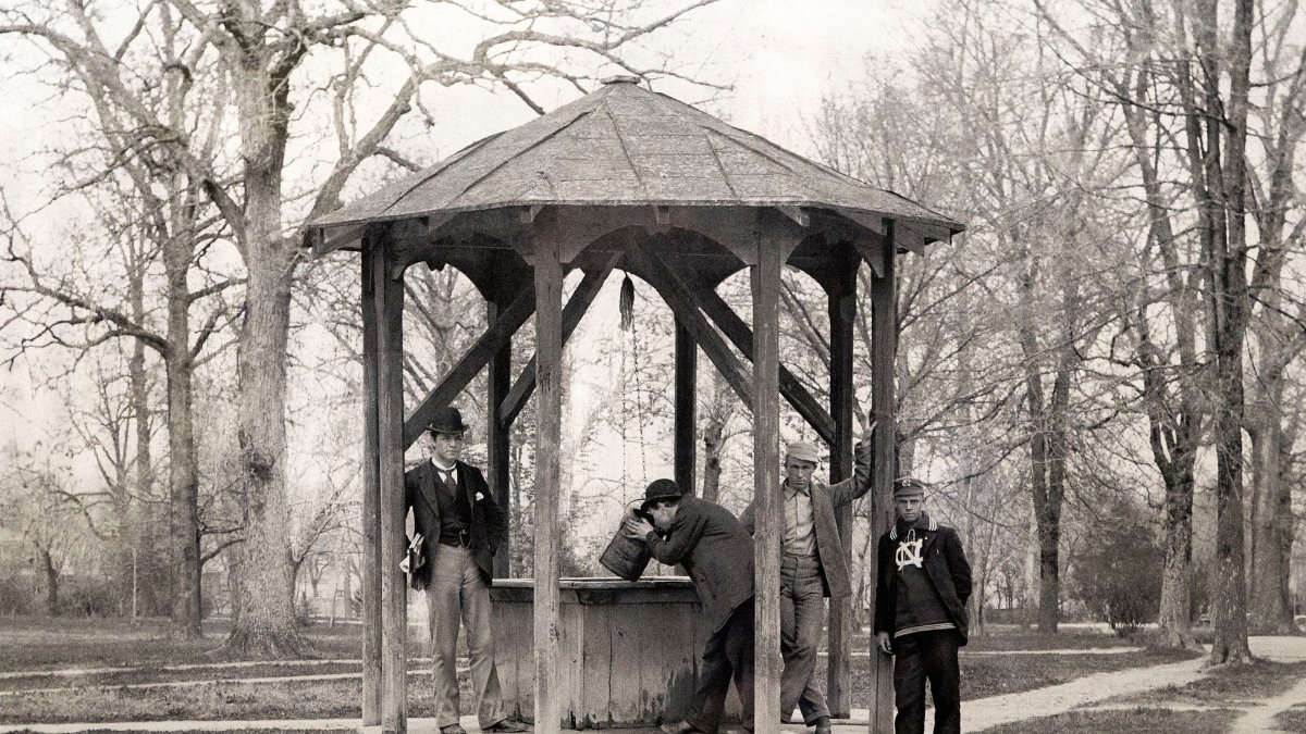 Photo of four men standing at the historic Old Well.