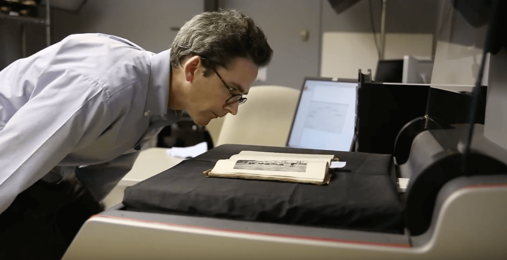 Person looks over a historic book as it is laying on a document scanner.