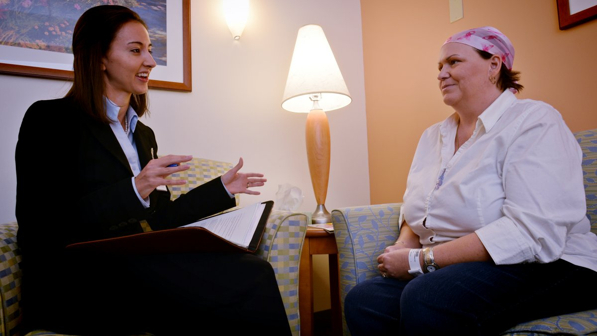 Second-year law student Kristi Nickodem, left, confers with cancer patient Chanda Holst at UNC Hospitals at the University of North Carolina at Chapel Hill.