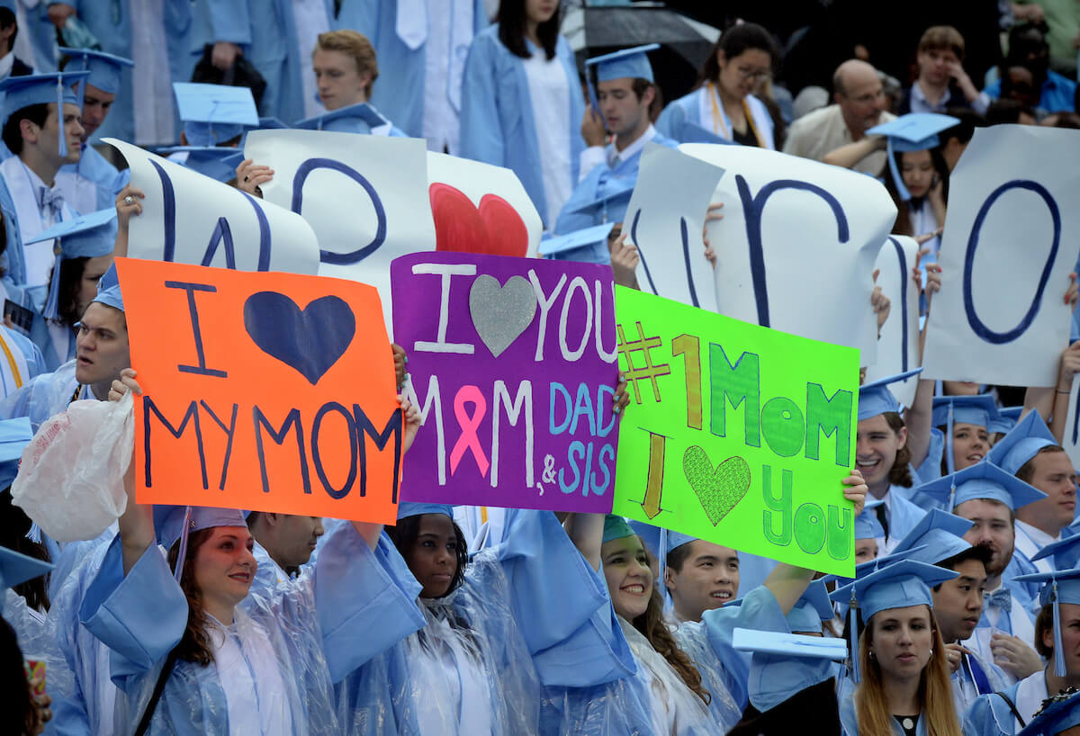 Graduates hold signs thanking their mothers