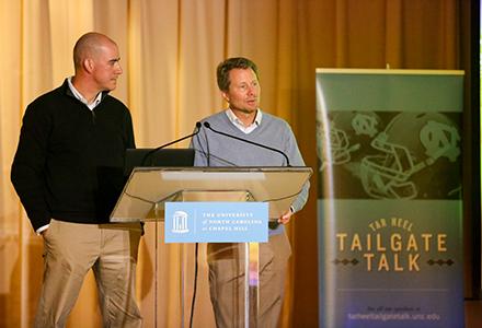Two man speaking at a podium.