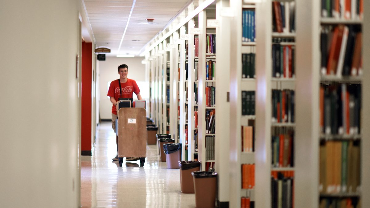 Brian O'Donnell walks down the library stacks.