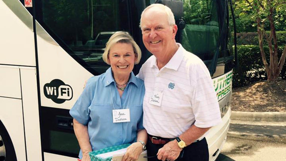 Woody Durham stands with woman in front of bus.