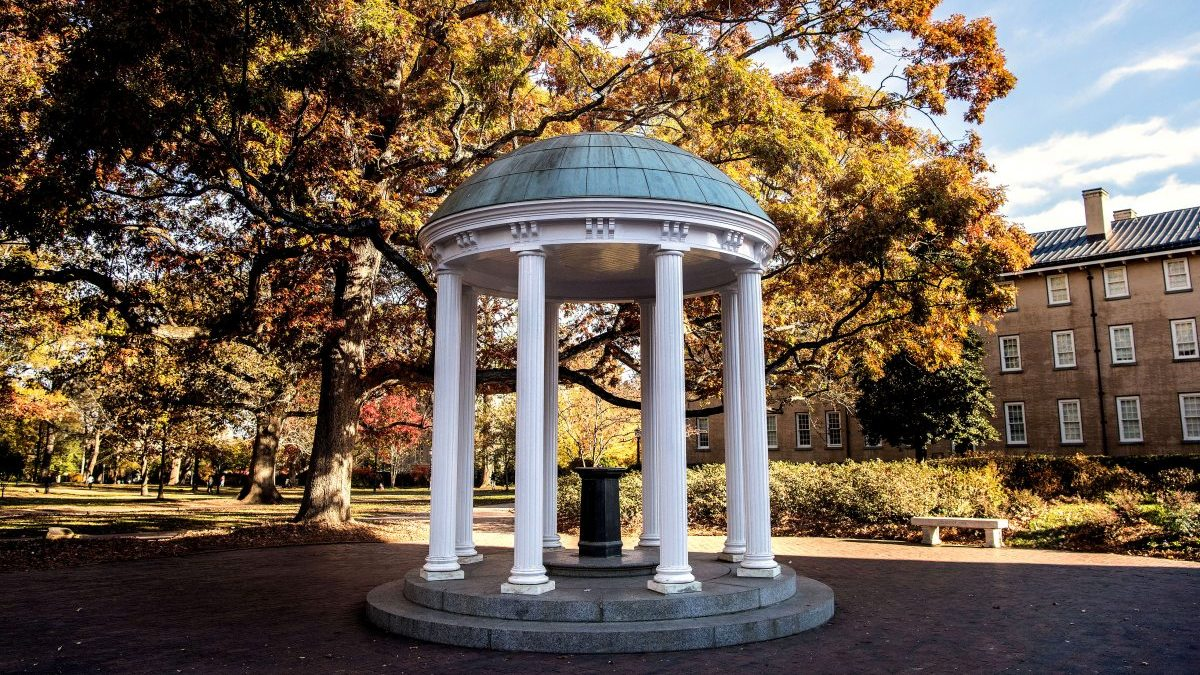 Old Well surrounded by trees with leaves changing color during fall.