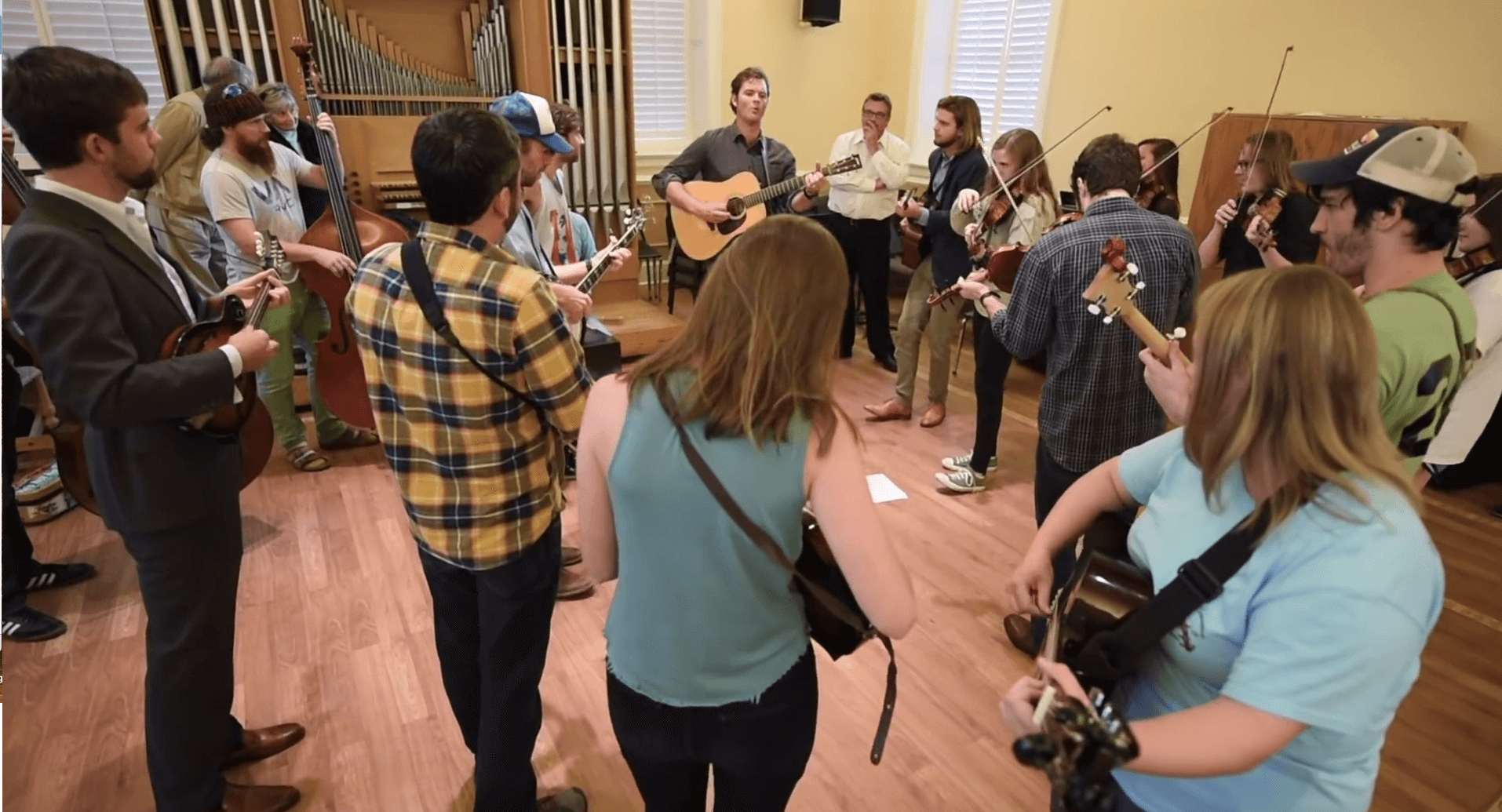 Group of adults play blue grass instruments.