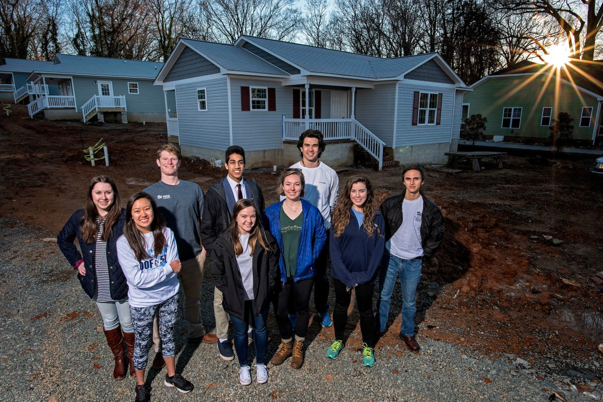 Group stands in front of a recently built house.