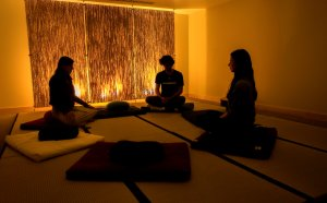 Three students sit on cushions in the meditation room in the Student Union.