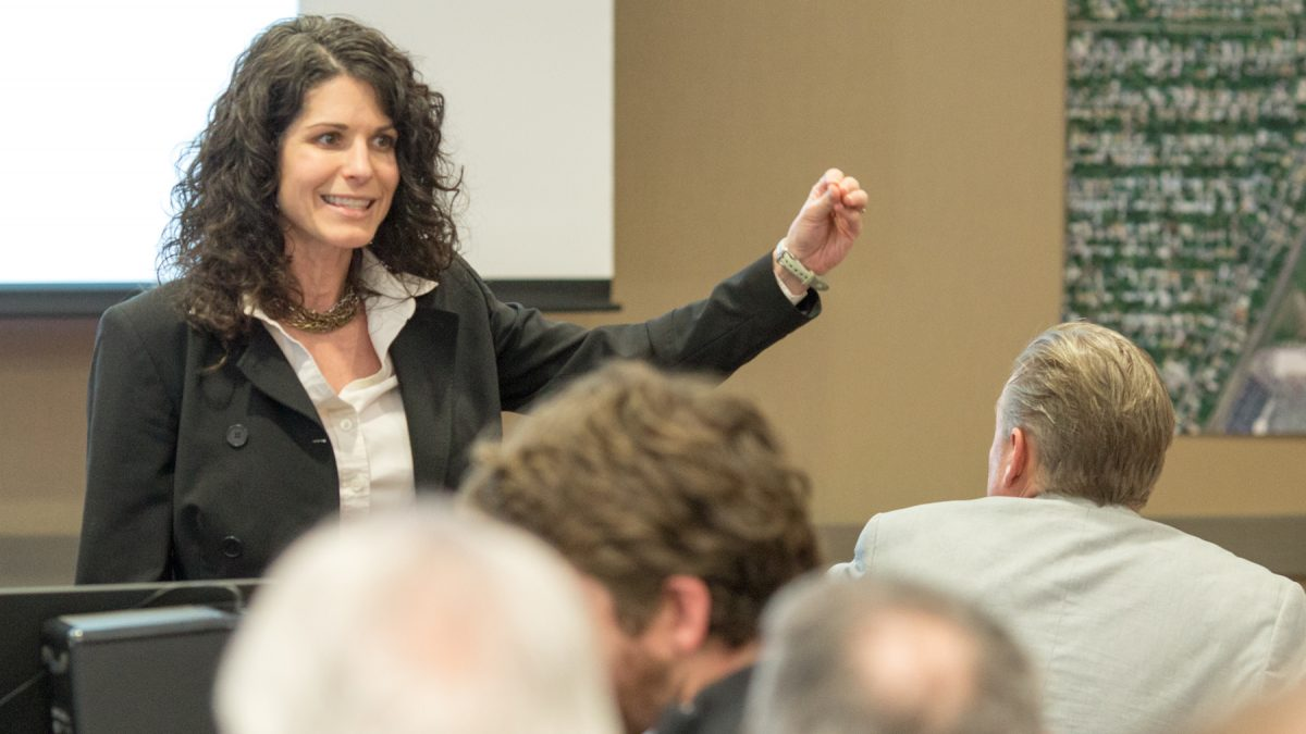 Instrucor Kara Millonzi gestures to a class.