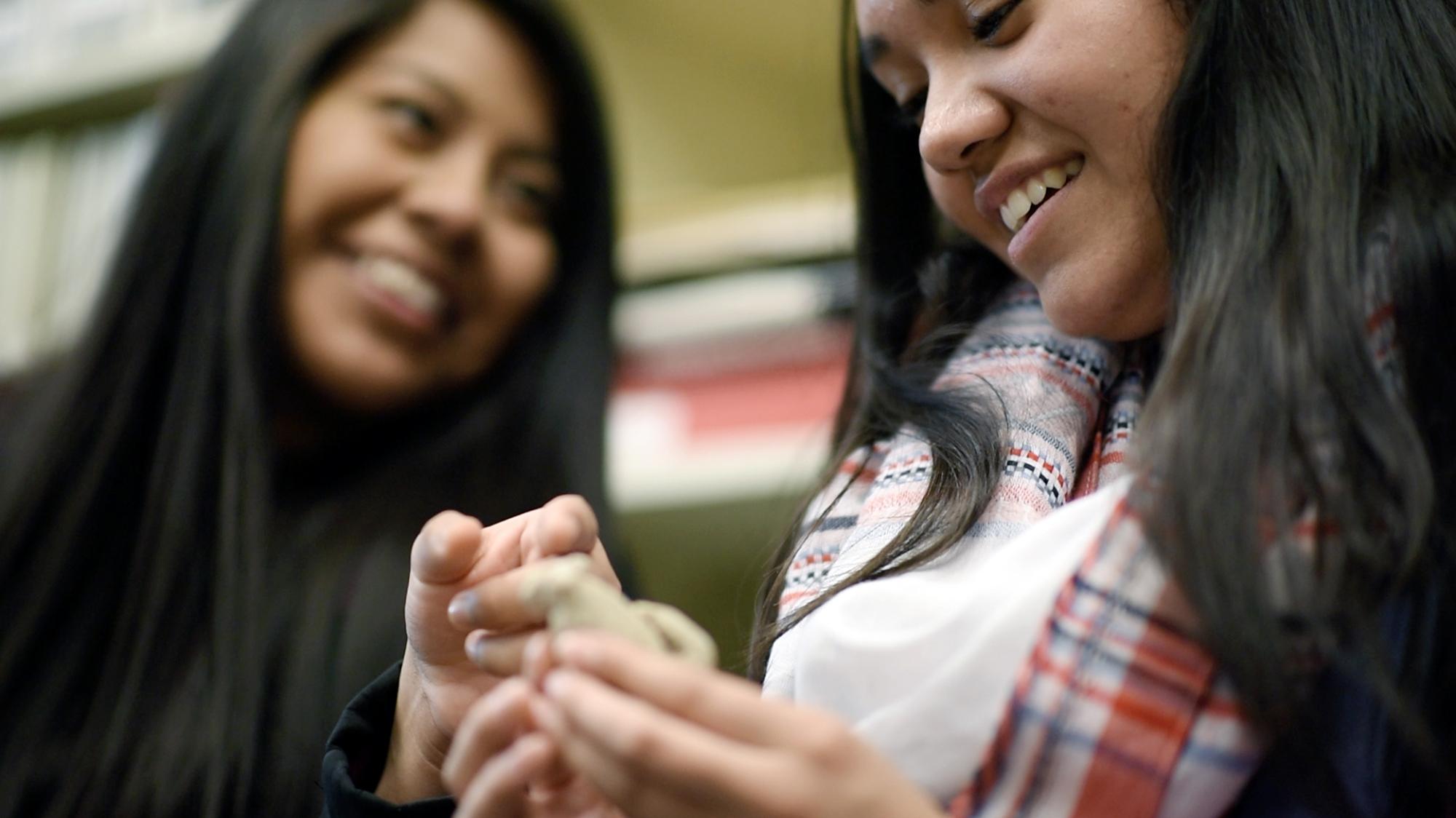Two female U.N.C. students examine an artifact.