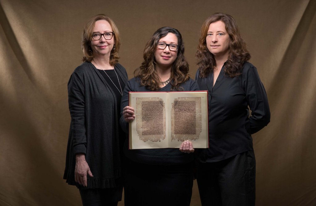 """an Chambers, Glaire Anderson and Laura Miller hold a facsimile of an 11th-century Arabic manuscript describing the flight of inventor Abbas ibn Firnas. """"The manuscript has yet to be incorporated into scholarship on aviation history,"""" said Anderson. Photo by Steve Exum."""