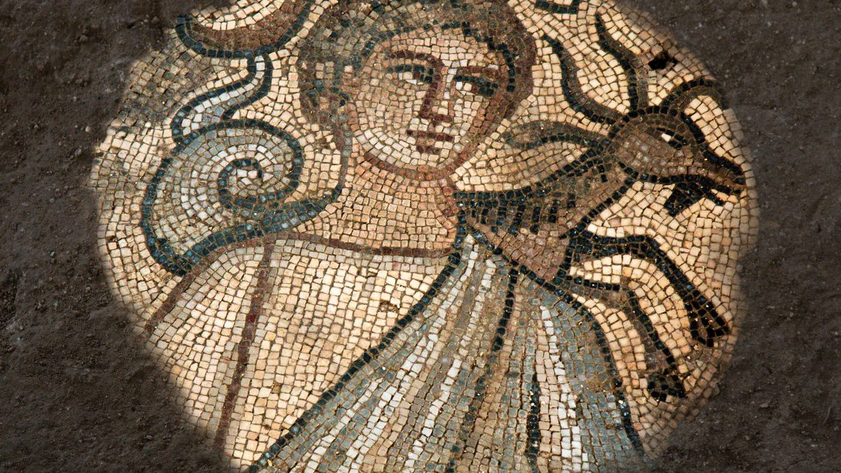 A mosaic structure depicting a a goat behind a man.