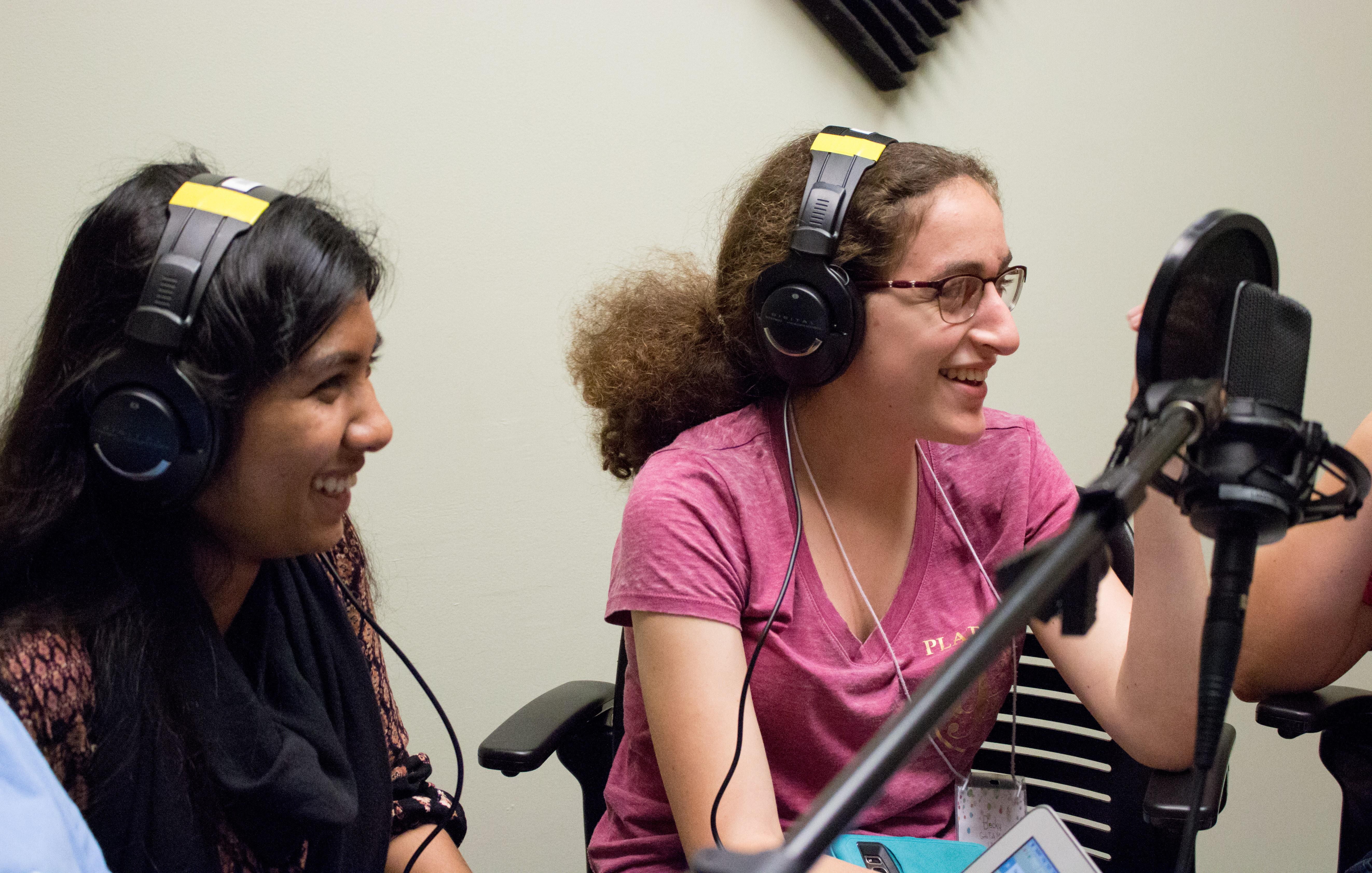 Two young women in the Girls talk Math program wear headphones and talk into a microphone.
