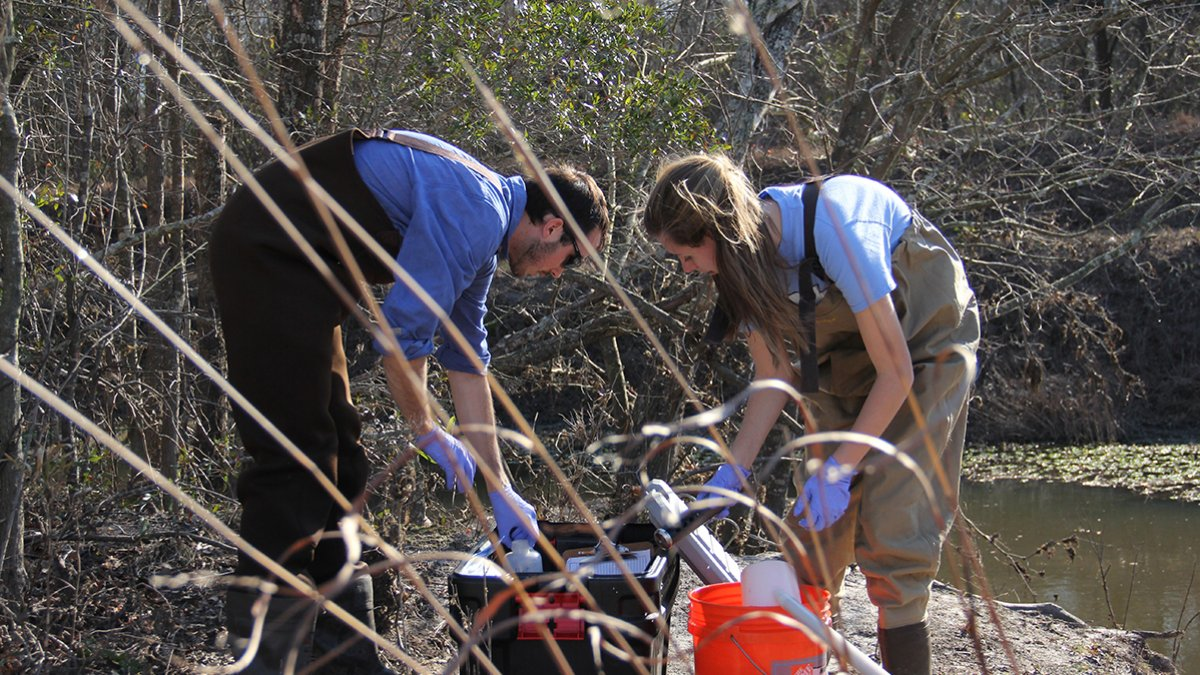 Two students remove trash from a stream.