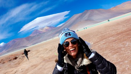 A woman wearing a Carolina knit cap smiles broadly at the camera with a barron brown field, mountains and a beautiful sky in the background