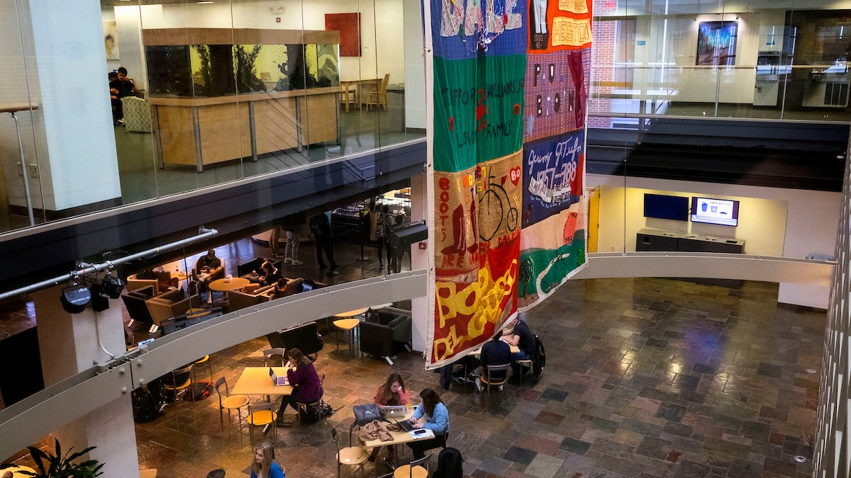 A panel of the AIDS Memorial Quilt hangs from the ceiling Student Union.