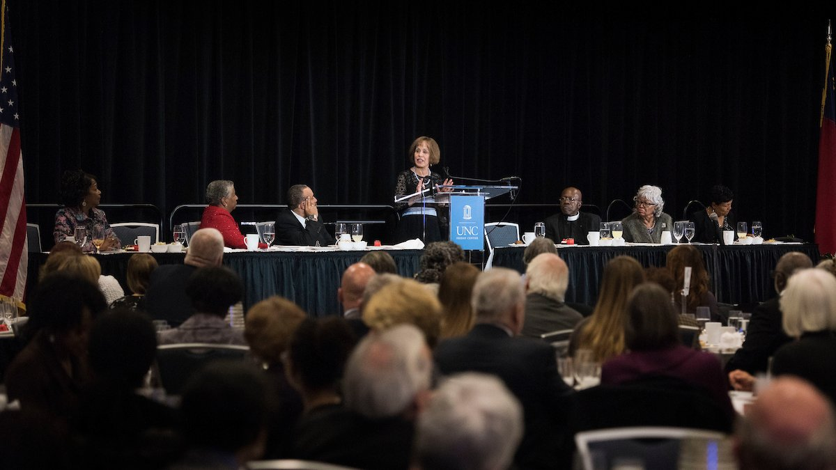 Chancellor Carol L. Folt speaks at a podium at a long table while the MLK banquet audience looks on.