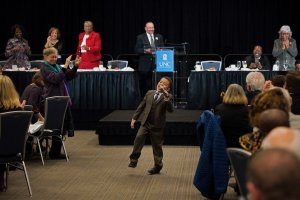 Caleb Serrano leans back, lifts a leg and sings into a microphone at the MLK banquet while the audience behind him stands and claps