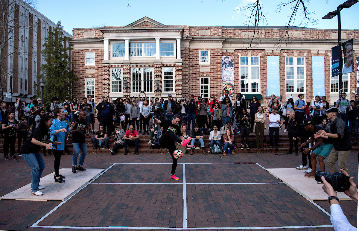 Indi Cowie juggles a soccer ball while the Dorrance Dance troupe dances on both sides of her and a crowd watches on