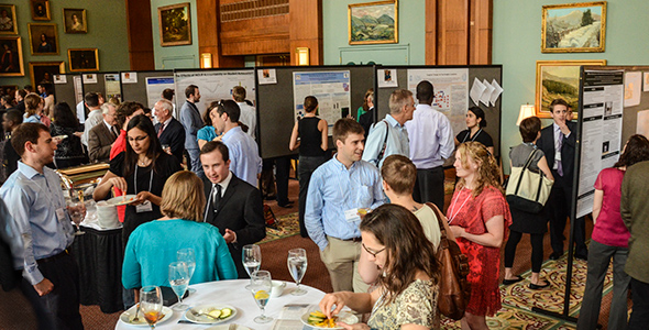 Students and guests mingle near a display of research posters.