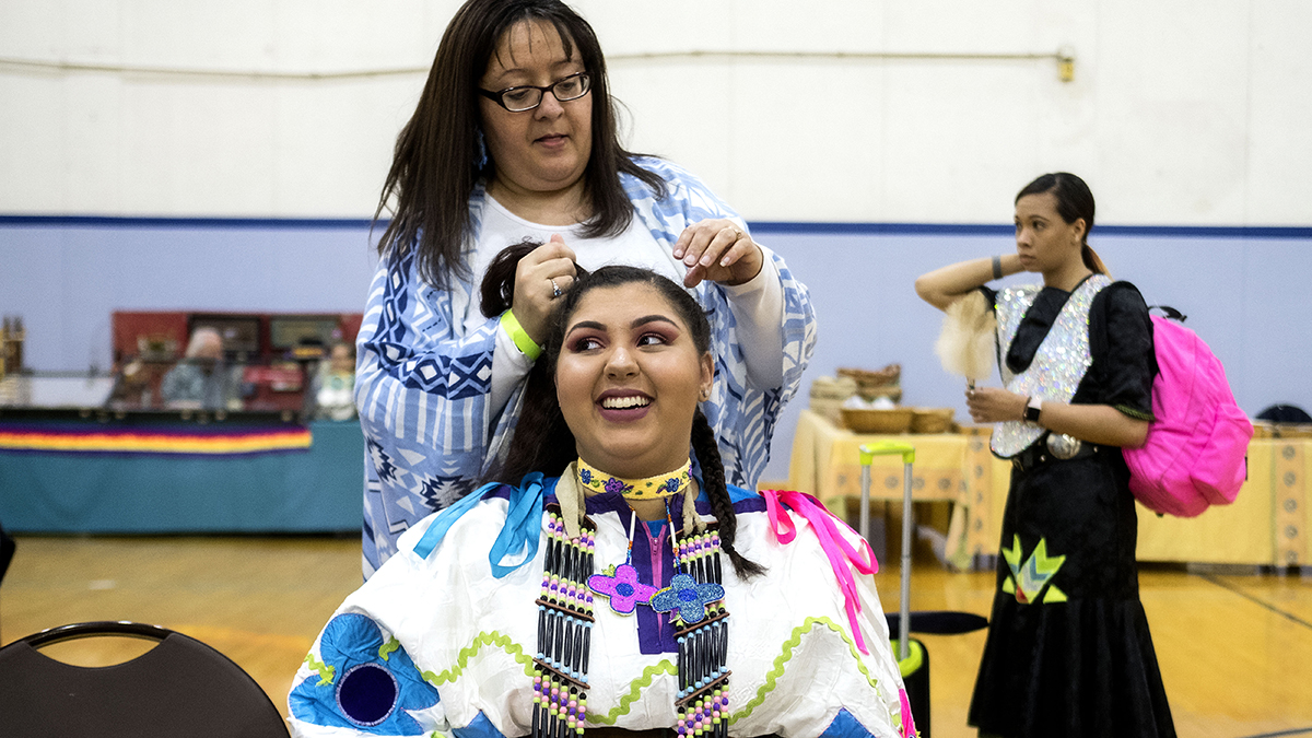 An adult helps a powwow dancer prepare for a performance.