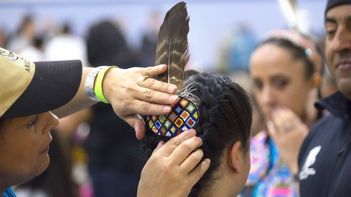 An adult helps place a feather in the hair of a powwow dancer.