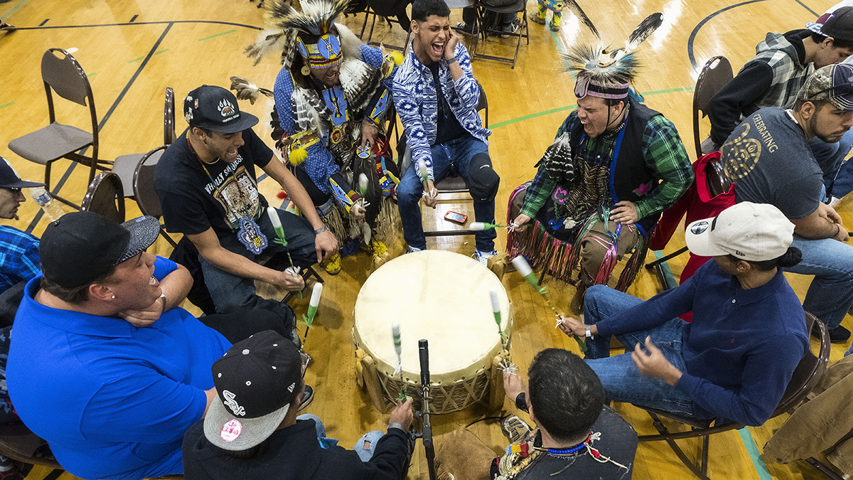 A group plays a tradional American Indian drum.