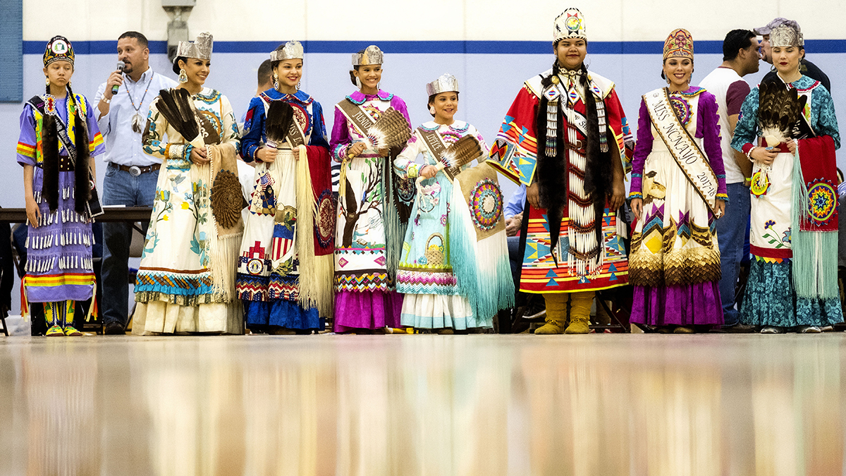 Powwow dancers stand in a line.