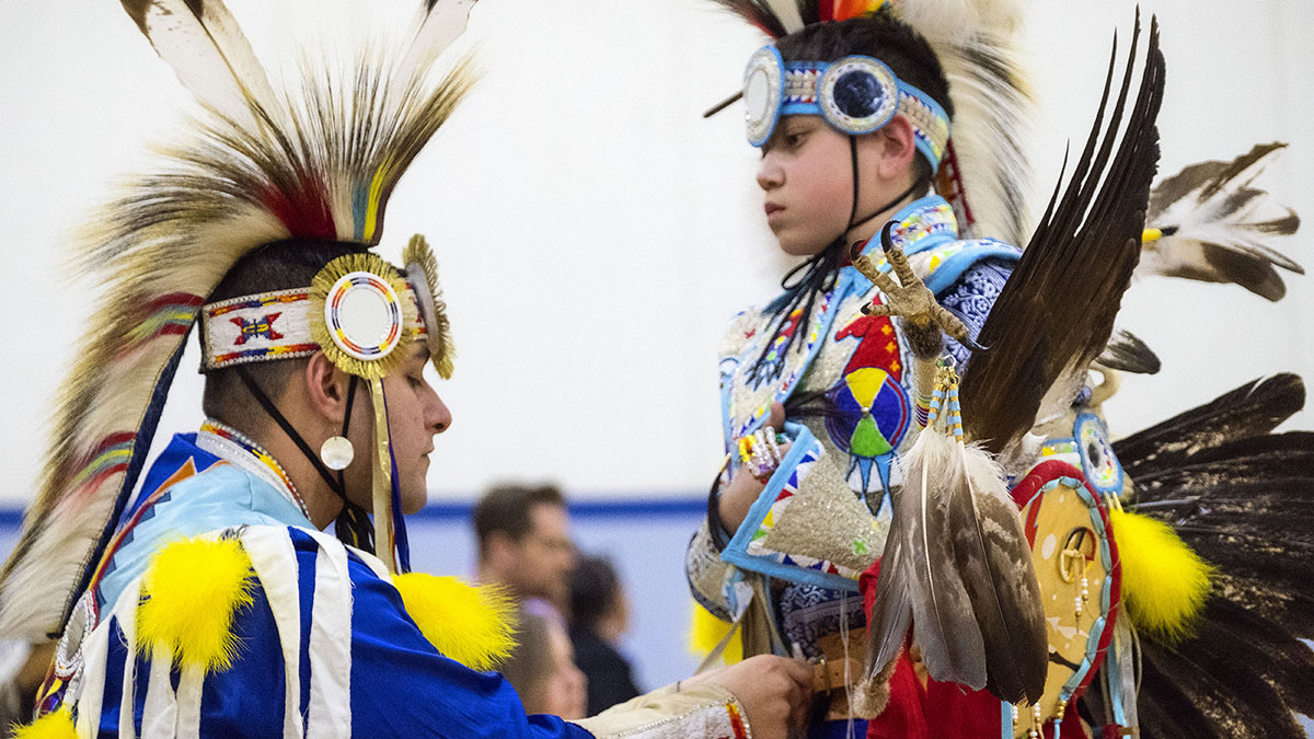 An adult helps a young powwow dancer with his regalia.