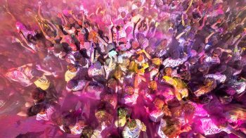 Students throw colorful powder in the air.