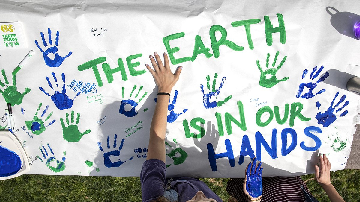 Students put hand prints on a paper banner
