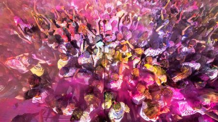 Students throw colorful paint into the air.