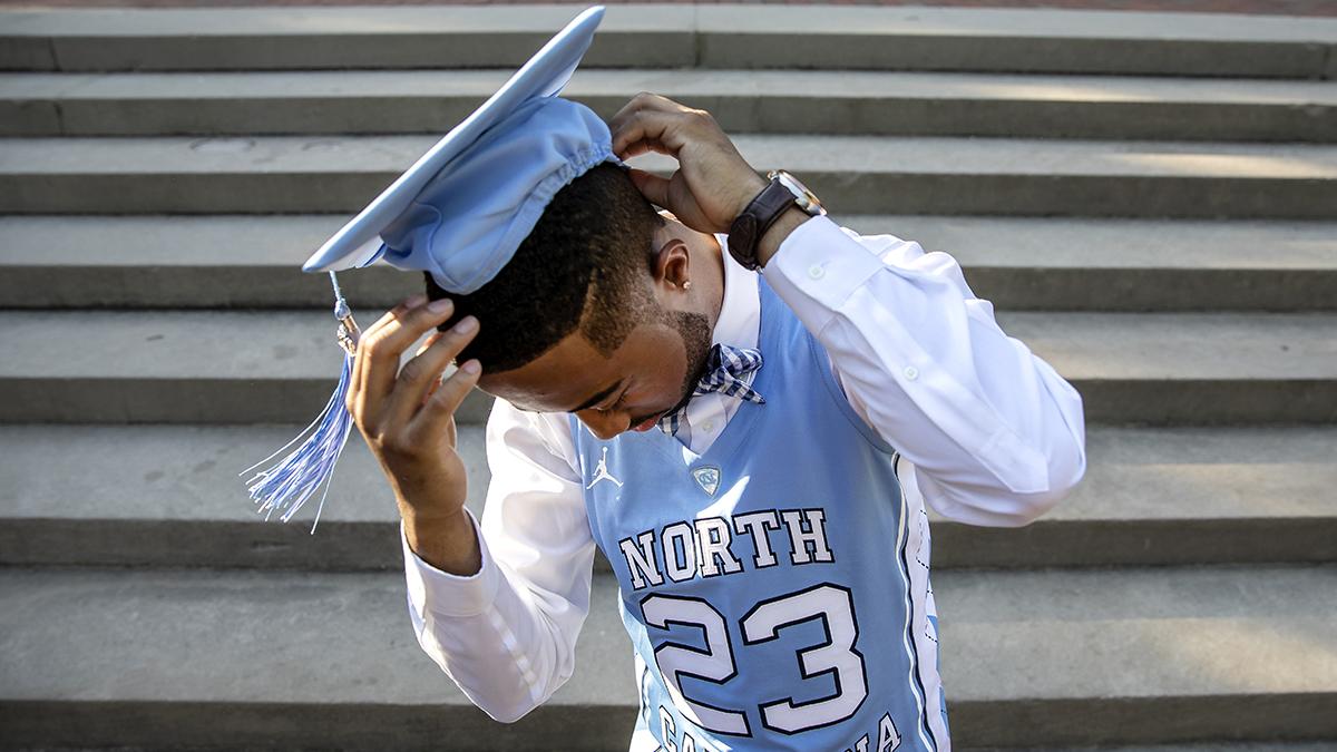 A student puts his cap on.