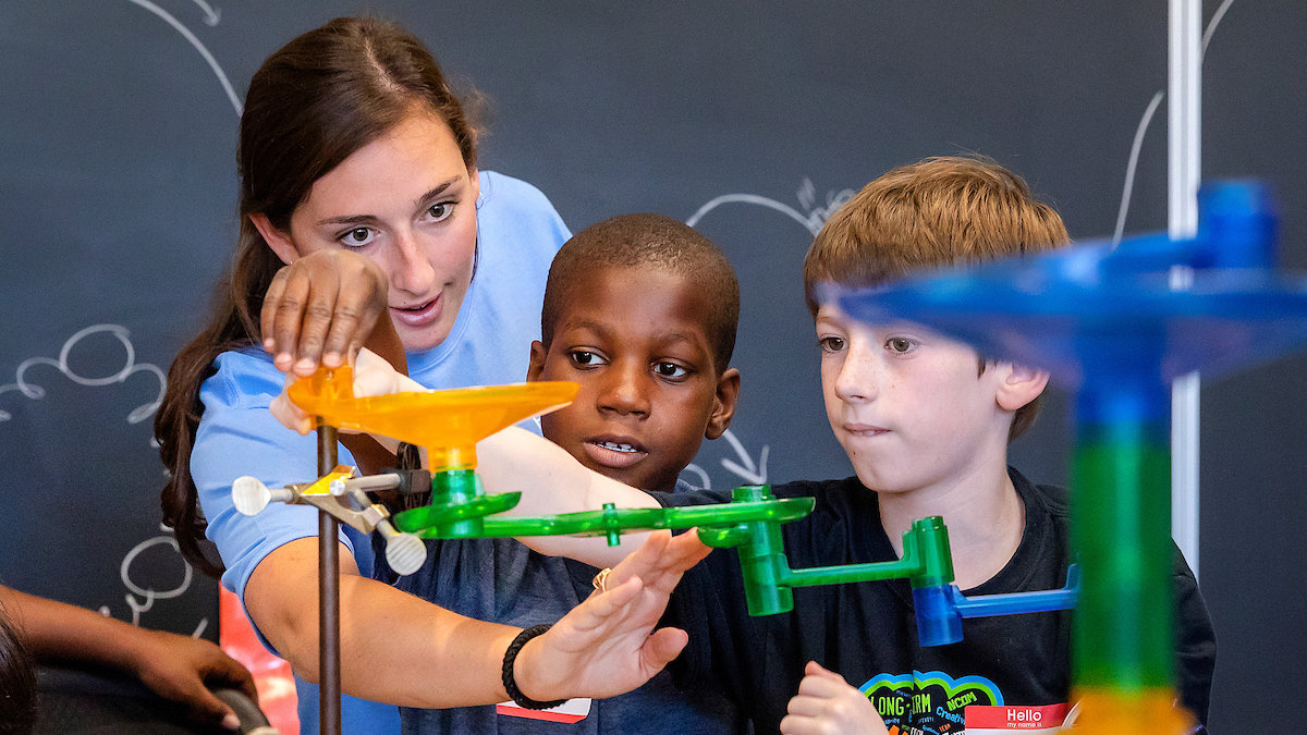 A Carolina student performs a science experiment.