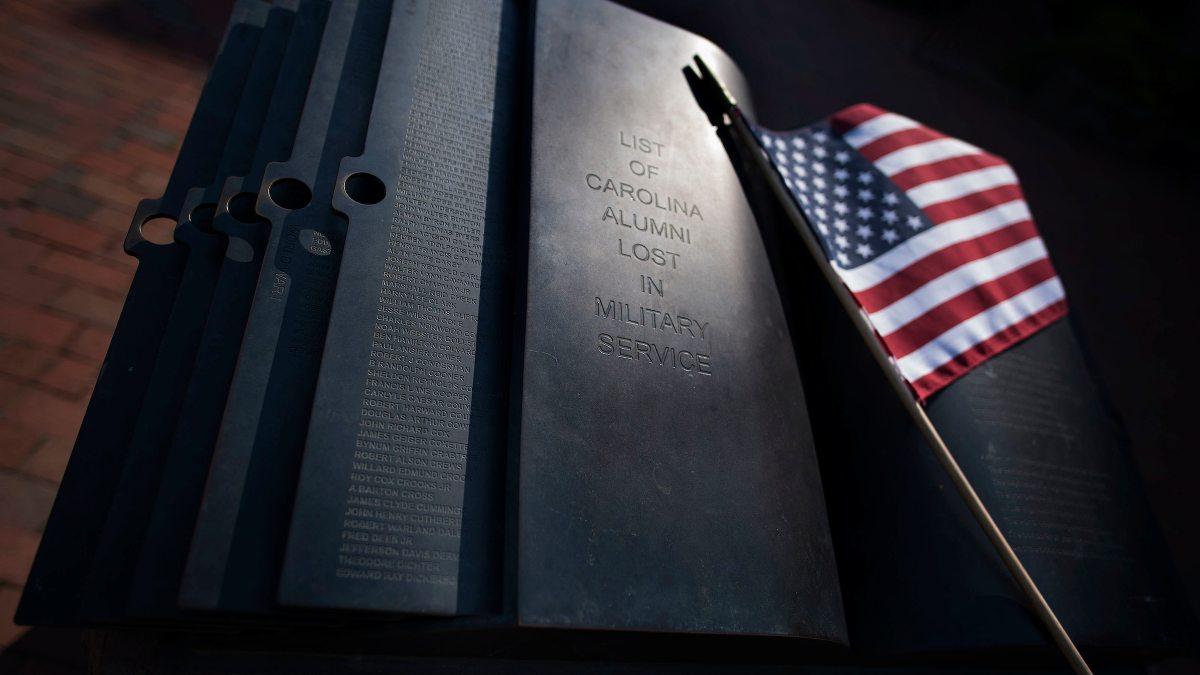 A flag leans against the memorial.