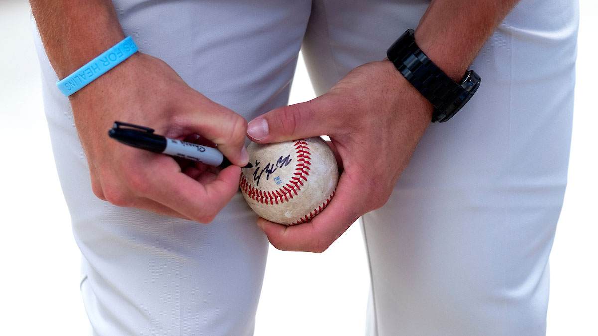 Baseball player signs a ball.