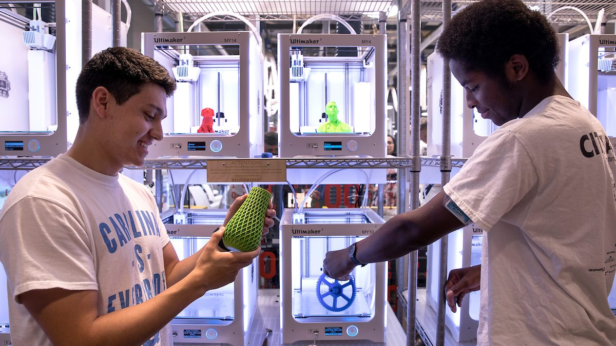 Two students use a 3D printer.
