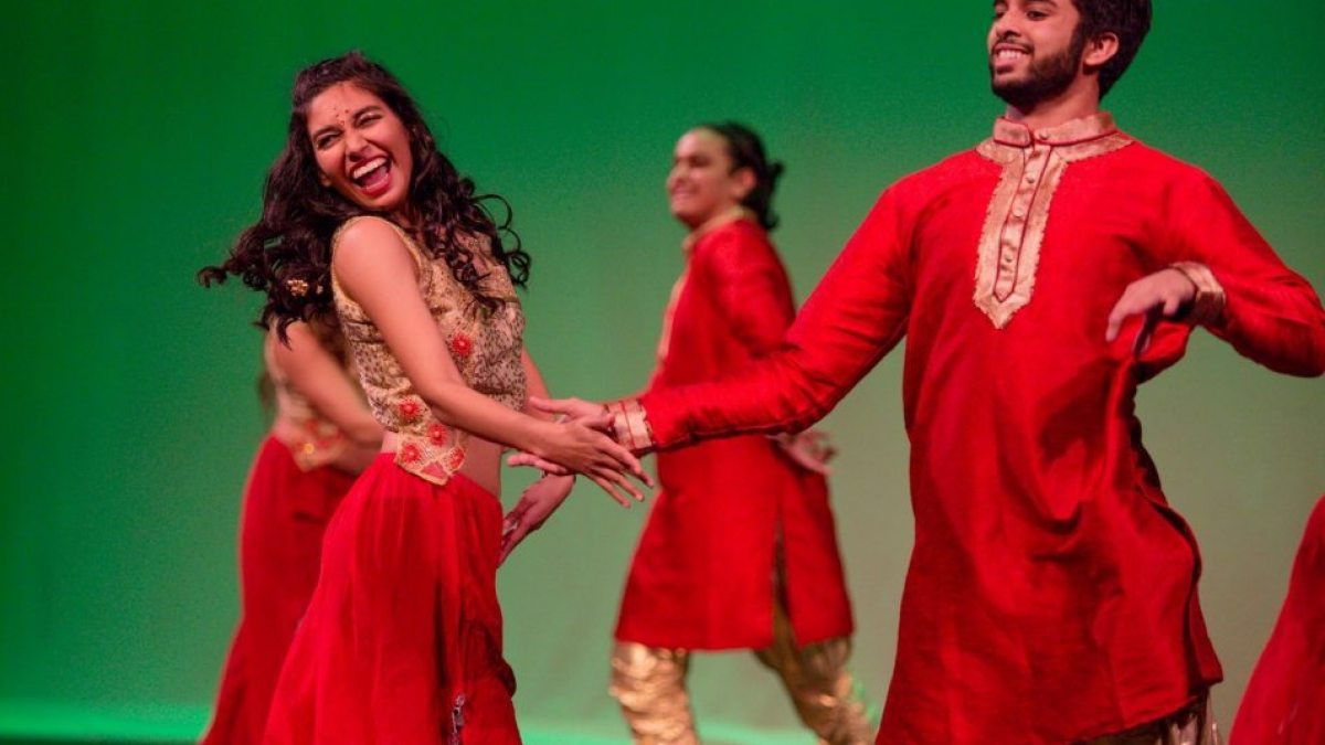 Matthews performs on stage dressed in red Bollywood costume