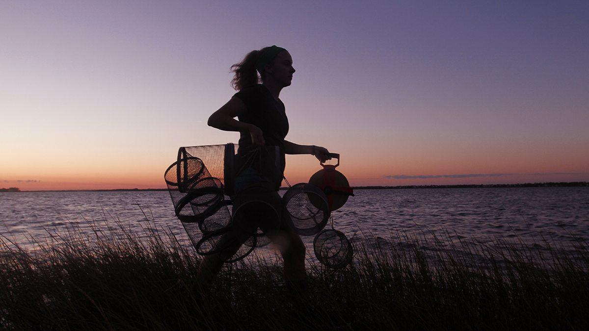 A women walks with nets.