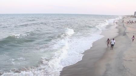 People walk on a beach.