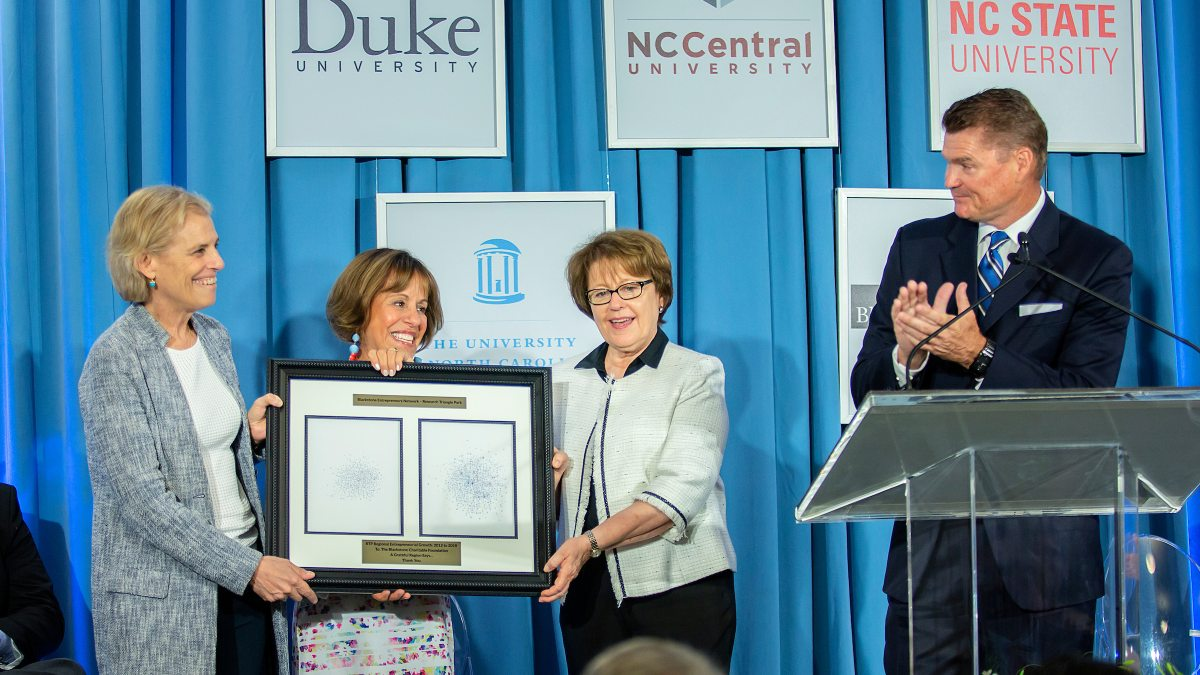 Amy Stursberg, Chancellor Carol L. Folt and Judith Cone hold a framed certificate