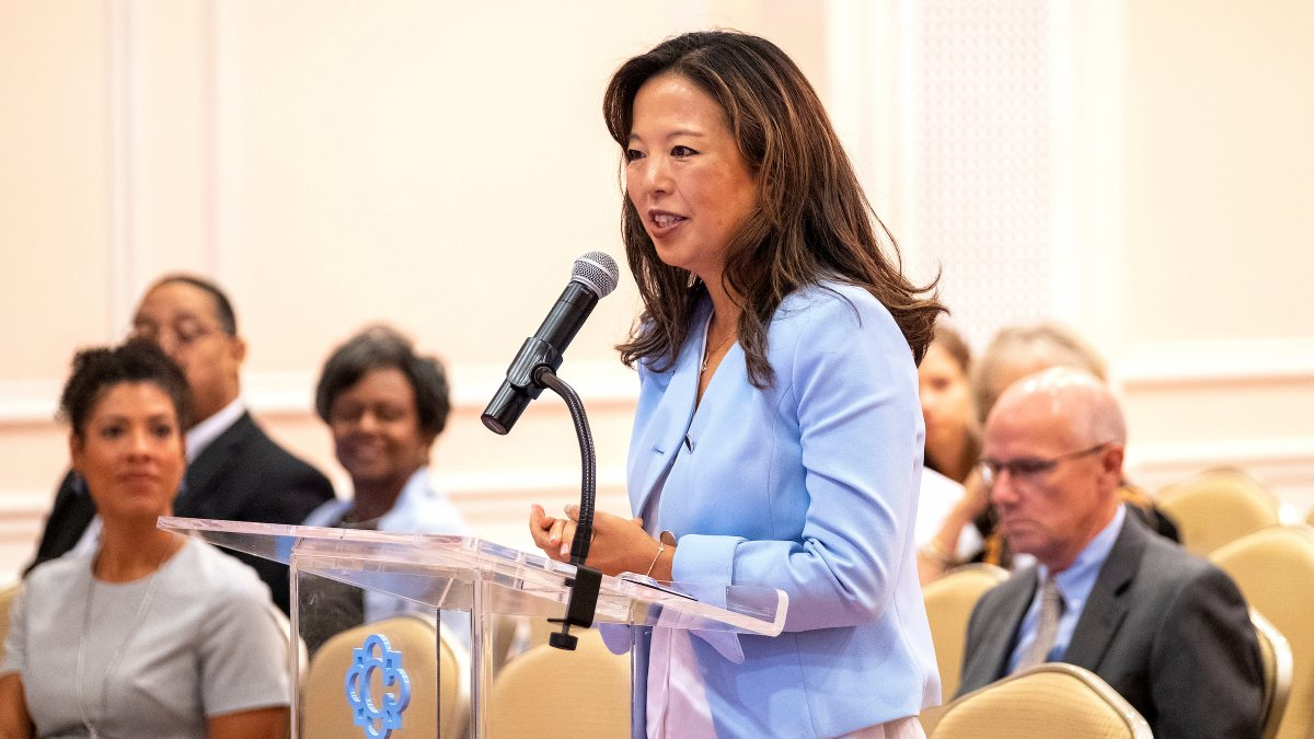 Jessica Lee speaks at a podium at a meeting