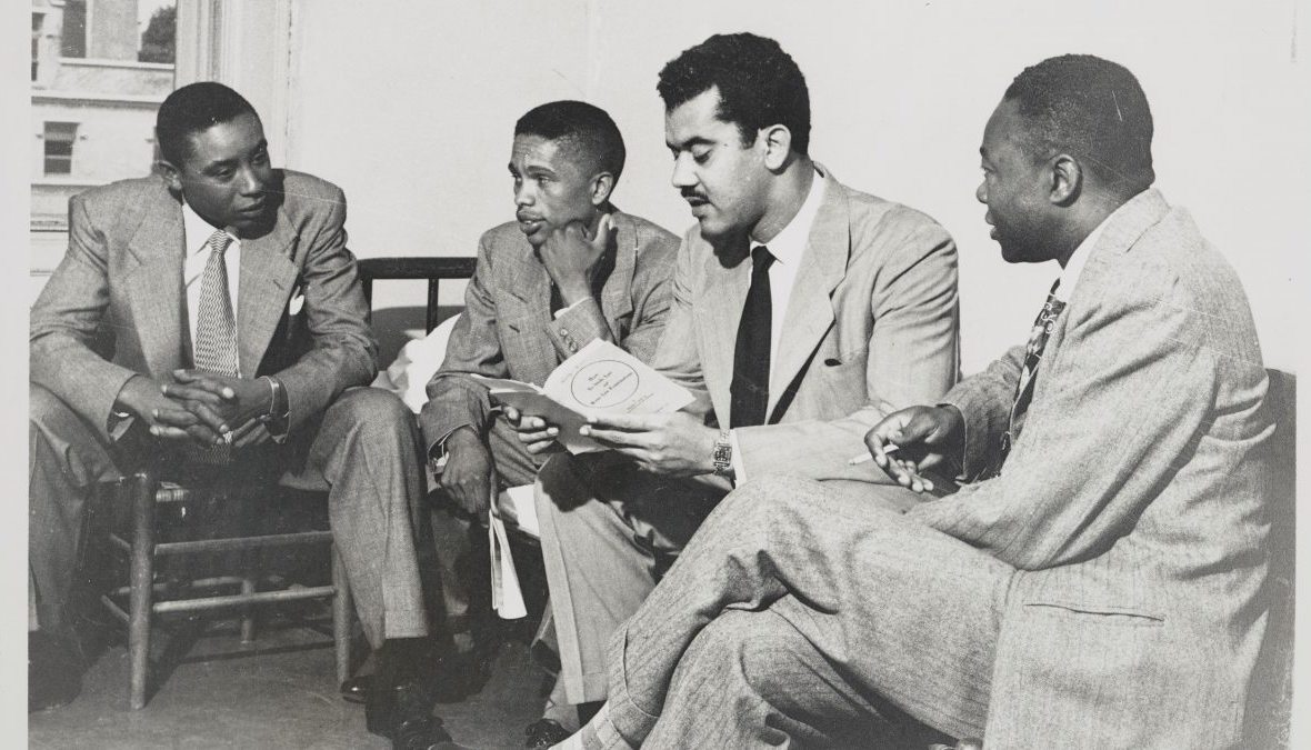 Floyd McKissick, J. Kenneth Lee, Harvey Beech and James Lassiter sit in chairs