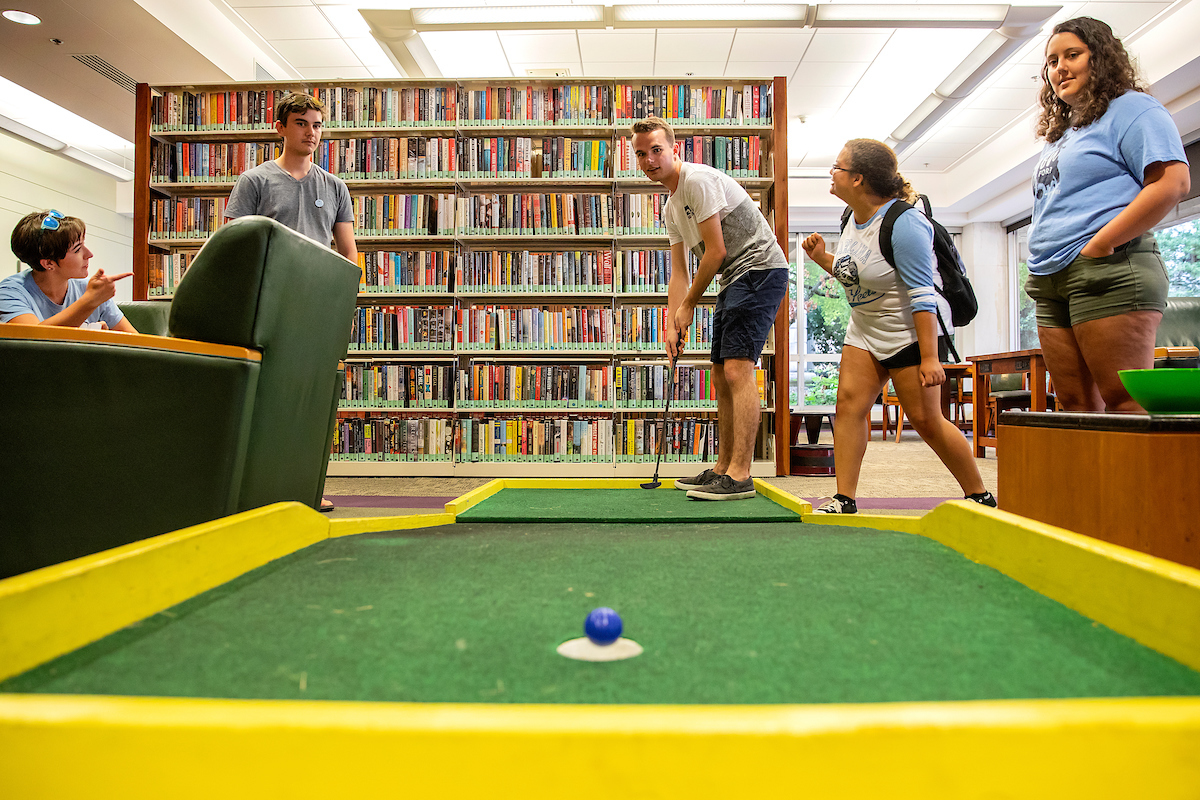 Students play mini golf in the Undergraduate Library.