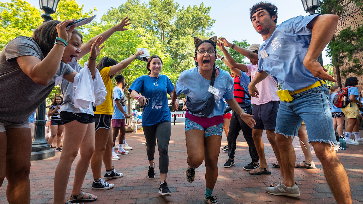 Students run and dance on campus.