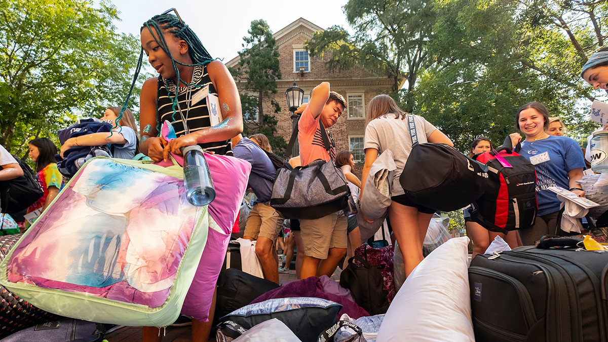 Incoming first-year students unload luggage.