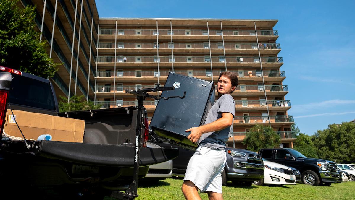 A man unloads a mini-fridge off a truck.